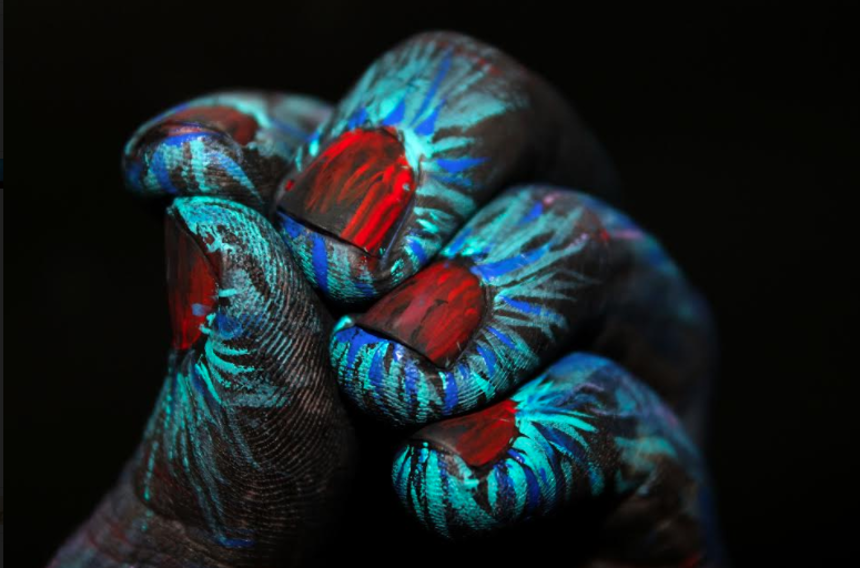 picture of painted hand with fingers bunched together and blue green swirls and red fingernails, artwork