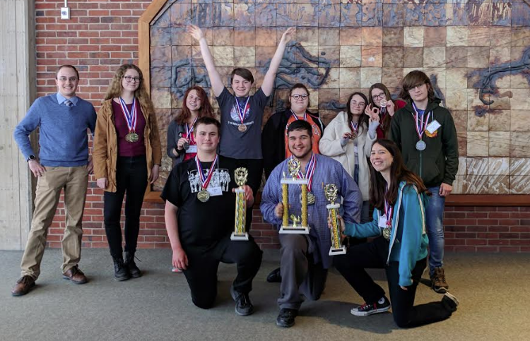 Photo of the team, The 2019 Cazenovia High School Academic Decathlon Team. Back Row: Ben Wightman (coach), Riley O'Brien, Alyson Woolbert, Carter Williams, Emma Lowry, Allie Everard, Gwen O'Brien, Alex Holmes. Front Row: Ian Melvin, Ronan DeFanti, Kate Martellock.
